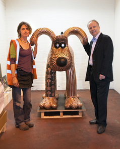 The Gromit sculpture. On the left its creator, Newport artist Stephanie Roberts; on the right The Royal Mint's Chief Engraver, Gordon Summers. © The Royal Mint.
