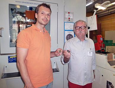 Von links nach rechts: Mitarbeiter der Staatlichen Münzen Baden-Württemberg Sasa Stricko und Künstler Othmar Kukula vor der Prägemaschine für die Normalprägung (Stempelglanz). Foto: Marco Müller.