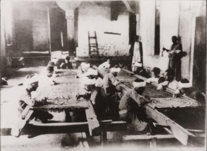 Photograph showing artisans at work at Dar al-Kiswah. 8.8 x 12 cm. Nasser D. Khalili Collection of Islamic Art © Nour Foundation. Courtesy of the Khalili Family Trust.