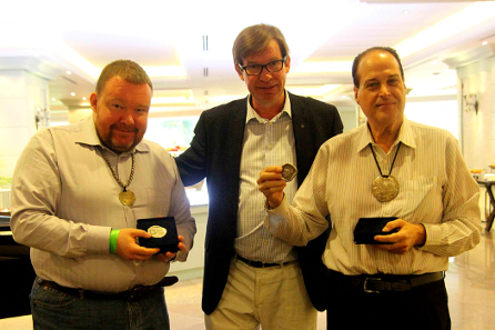 Vasilijs Mihailovs (left); I.A.P.N. member and Thai coinage expert Jan Olav Aamlid (center); Ronachai Krisadaolarn (right) at the award ceremony in Bangkok. Mihailovs and Krisadaolarn are displaying their I.A.P.N. Book Prize Medals.
