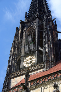Tower of St. Lambert's Church, Münster. Above the clock three iron cages are suspended in which the corpses of the executed Anabaptists had been put on display. Photograph: Wikipedia / Jule Hintzbergen. CC-Lizenz 3.0.