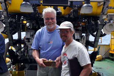 Craig Mullen (links) und der Historiker Bob Evans (rechts) halten einen der fünf Goldbarren. Copyright: Odyssey Marine Exploration, Inc., www.OdysseyMarine.com.