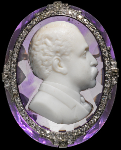 1157: Portrait of a French politician (Raymond Poincaré?). Paris, end of 19th cent. 4.4 x 3.8 x 1.6 cm. White agate layer, embedded in large, cut amethyst. Mounted as brooch in gold and platinum with brilliants. On golden setting signed MELLERIO DITS MELLER PAIX PARIS. Estimate: 10,500 euros. Intact.