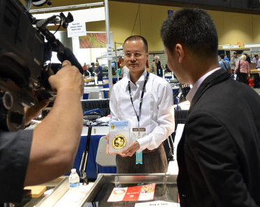 Mr. Chen Haomin, Chairman of Coin in Coin, Guangzhou, China and General Manager of the Guangzhou PCGS Submission Center, holds a PCGS-certified 1996 China Unicorn 1 kilo gold coin during an interview with a Los Angeles television station during the June 2014 Long Beach Expo./ Photo credit: Donn Pearlman.