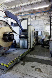 Coil being fed into a punching press.