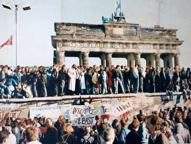 Menschenmengen auf der Berliner Mauer Ende 1989 nach dem historischen Mauerfall. Im Hintergrund das Brandenburger Tor, Symbol der Wiedervereinigung Deutschlands. Foto: Lear 21 / Wikipedia. http://creativecommons.org/licenses/by-sa/3.0/