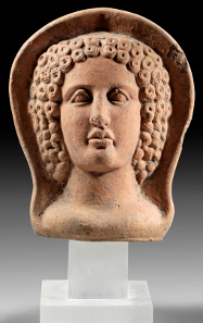 Lot 484: Protome of a young woman. Etruscan, 4th-3rd cent. BC. Slightly under life-sized head of a young woman with a curly coiffure capite velato. Estimate: 1,000,- euros. Provenance: From the Dr. V.Z. Collection, Switzerland, acquired in the 1950s/1960s, loaned to the Archaeological Collection of the University of Zurich for an exhibition between 1986 and 2001.