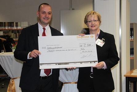 Arnd Gollan überreicht den symbolischen Scheck über 2.500 Euro an Dr. Bettina Schmidt-Czaia.