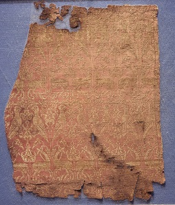 Fragments of the funerary robe of Henry VI, red-and-gold lampas silk, tomb of Henry VI, Palermo, Sicily, AD 1197. © The Trustees of the British Museum.