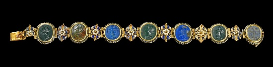 Lot 494: Golden armlet with rosettes made in dark blue and white enamel and 7 gemstones. France or Switerland, around 1780. One of the rosettes is broken, otherwise intact. Estimate: 9,000,- euros.