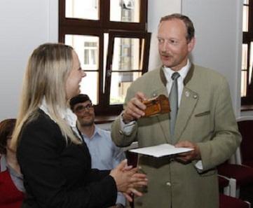 Veranstaltungs-Organisatorin Sandra Grötzschel übergibt den Hauptpreis des Motto-Wettbewerbs an Prof. Carsten Drebenstedt. Foto: Torsten Mayer.
