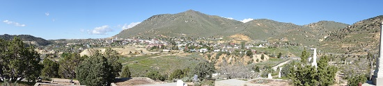 View from one of the cemeteries to Virginia City, or rather what is left of it. Emerging from the hill, the silver ore runs underneath the city, right to the houses in the valley. Photograph: UK.