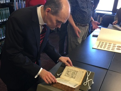 Dr. Woytek examining a 1567 edition of works by Guillaume Du Choul.