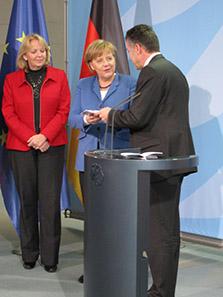 Staatssekretär Werner Gatzer übergibt der Bundeskanzlerin Angela Merkel ein Set der neuen 2-Euro-Gedenkmünze