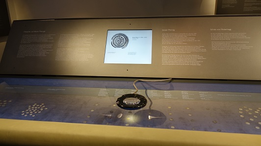 Big magnifying glasses not only enable visitors to get a larger image of the coins in the vitrines, but they are also presented with additional information of a screen. Photo: KW.