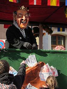 Sepp Blatter thront auf einem Fasnachtswagen, der geschmückt ist mit Bündeln von Geld. Foto: UK.