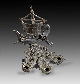 Lot 234: Oceanus-shaped bronze lamp with attachment in the shape of a ship. Roman, 1st-2nd cent. AD. From the Shlomo Moussaieff Collection. With export permission from the Israel Antiquities Authority. Estimate: 50,000,- euros. From Gorny & Mosch sale 248 (June 30, 2017), No 234