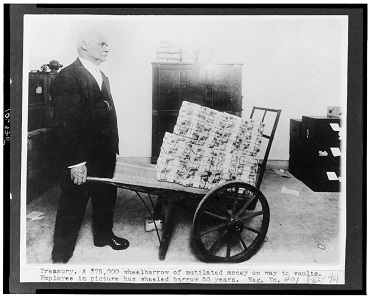 Employee with a wheelbarrow full of banknotes to be laundered, taken between 1909 and 1925. Photo: Library of Congress, Prints &Photographs Division (LC-USZ62-106975).