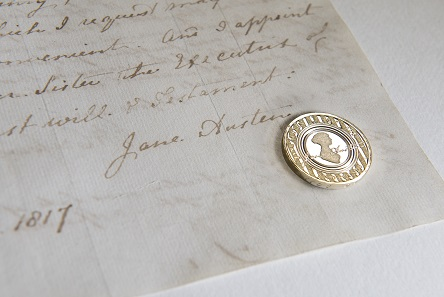 Jane Austen coin against Jane Austen's signature on her will. Photo: Courtesy of The National Archives, Kew.