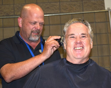 History's Pawn Stars celebrity Rick Harrison makes the first pass of the electric cutter as NGC Vice President Miles Standish gets his head shaved to raise money for the Austin-based Standish Foundation for Child & Family Centered Healthcare and the American Numismatic Association. Photo credit: Donn Pearlman.