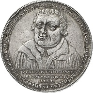 Medal 1717 on the 200th anniversary of the Reformation. Estimate: 250 euros. From Künker sale 297 (September 27, 2017), No. 3029. – This extremely rare medal shows how Luther crushes the power of the Pope, symbolized by the tiara, with the truth (VERITAS) and the Holy Scripture (S[C]RIPTVRA).