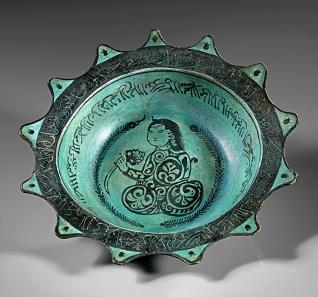 Los 715: Glasierte sternförmige Schale aus grauem Ton mit türkisgrüner Grundierung und schwarzer Bemalung. Islamisch, 12./13. Jh. Dm. 23,5 cm. Taxe: 1.000 EUR.