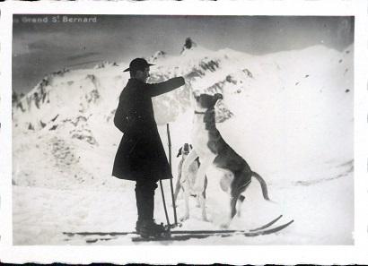 Diese Aufnahme von 1924 zeigt einen Skiläufer und zwei Bernhardiner vor dem Grossen Sankt Bernard. Foto: Dr. Gustav Nünnicke – Günter Hiess / Wikimedia Commons / CC BY-SA 3.0.