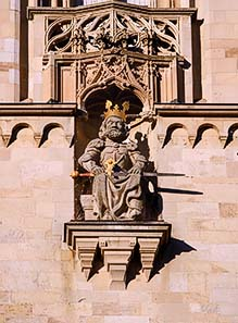 Fig. 4: Copy of the statue of Charlemagne on the southern tower of the Grossmünster  (the original can be seen in the crypt). Native citizens of Zurich will tell you that this stone statue will throw bread from the tower of the Grossünster as soon as he hears the 6th stroke of the church's bell. This is absolutely true. Or would you believe a stone statue being able to hear? Foto: roland, zh / Wikipedia