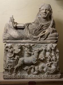 Eine reich gekleidete etruskische Dame liegt wie zu einem Bankett auf Kissen gebettet und bildet somit den Deckel einer Aschenurne; sie stellt wahrscheinlich die Verstorbene dar. Volterra; Alabaster; 2. Jh. v. Chr. © Archäologisches Museum Frankfurt.