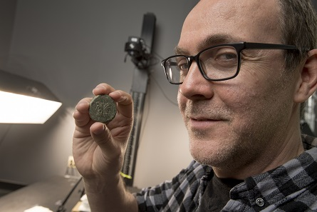 Rick Hale, who has spent the past several years digitizing the Badian Collection of Coins of the Roman Republic, examines one of his coins. Photo: Nick Romanenko, Rutgers University.