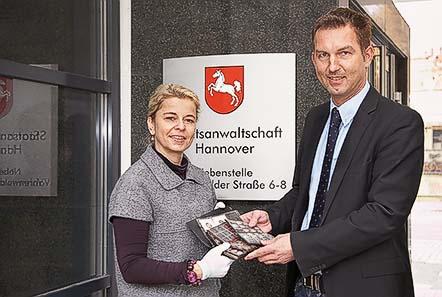 Der ermittelnde Staatsanwalt, Oliver Eisenhauer, übergibt der Numismatikerin des Museums August Kestner, Dr. Simone Vogt, die 618 Münzen.
