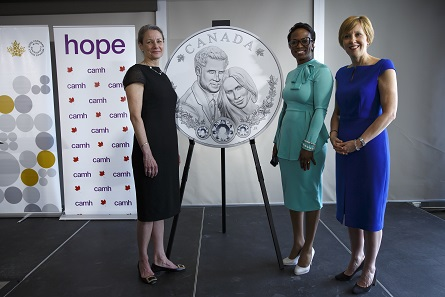 Royal Canadian Mint President Sandra Hanington, CAMH Foundation President Deborah Gillis, and Parliamentary Secretary to the Minister of International Development Celina Caesar-Chavannes (from left) unveil a silver collector coin celebrating the royal wedding of Prince Harry and Ms Meghan Markle in Toronto on May 9, 2018.