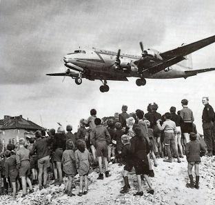 """Berliner beobachten die Landung eines Flugzeuges der Westallierten. Foto: Cees Steijger (1991), """"A History of USAFE"""", WikiCommons."""