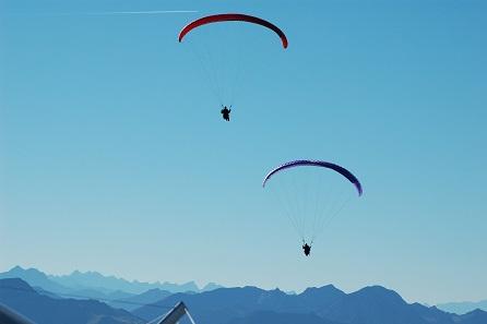 Gleitschirme vor den Alpen. Foto: TobiWanKenobi / Wikicommons.