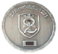 """A Challenge Coin of the 2nd company of the Jägerbatallion 291. The obverse shows the outline of a crest as well the Bundeswehr insignia in the background, the number 2, an oak leaf (the beret flashes of Jäger troops), the year of issue (censored), and a crown. A serial number (censored) was added underneath. The reverse features the outline of France and the battalion's deployment location in Illkirch-Graffenstaden, oak leaves, and their unofficial motto """"Tapfer und Treu"""" (engl. Brave and Loyal). Photo: LS."""