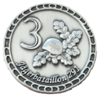 """This Challenge Coin was minted on behalf of the 3rd company of the Jägerbatallion 291 to mark the UN MINUSMA mission in Mali. The obverse features the number 3 as well as a combat helmet and oak leaves (the beret flashes of Jäger troops). The reverse depicts the outline of Mali, the deployment location Gao, the deployment unit, the time of deployment, a serial number (censored) as well as """"Unteroffizerkorps Sicherungskompanie Gao"""". Photo: LS."""