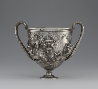 Cup with Masks. Roman, 1-100 CE. Inscription: MERCVRIO AVGVSTO Q DOMITIVS TVTVS EX VOTO (To Augustan Mercury, Quintus Domitius Tutus in fulfillment of a vow). Find-spot: Berthouville, France. Silver. H. 15.8 cm; W. 19 cm; Diam. 13.3 cm. Bibliothèque nationale de France, Paris: inv. 56.9. Photo: Tahnee Cracchiola © Getty-BnF.