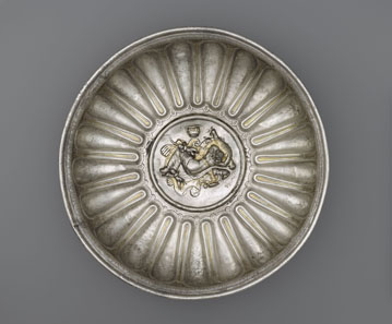 "Bowl with a Medallion Depicting Omphale. Roman, 1-100 CE. Inscribed: ""MERCVRIO AVGVSTO Q DOMITIVS TVTVS EX VOTO "" (To Augustan Mercury, Quintus Domitius Tutus in fulfillment of a vow). Find-spot: Berthouville, France. Silver and gold. H. 8.2 cm; Diam. 28.9 cm. Bibliothèque nationale de France, Paris: Inv. 56.11. Photo: Tahnee Cracchiola © Getty-BnF."