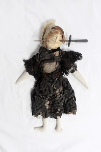 'Poppet' of stuffed fabric in Edwardian-style black dress with stiletto through face. South Devon, England , 1909-13. 38 cm. © The Museum of Witchcraft and Magic, Boscastle.