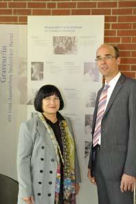 Designerin Sneschana Russewa-Hoyer vor der neugestalteten Tafel zu Graveuren, daneben Geschäftsleiter Dr. Andreas Schikora.