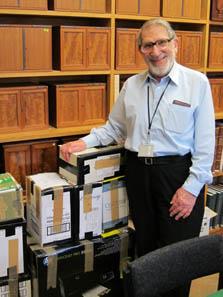 Ted Buttrey vor einem Stapel Kataloge, wie er sie an die numismatischen und historischen Institute der Welt verschickt. Die von Sammlern und Münzhandlungen kostenlos zur Verfügung gestellte Exemplare versendet er häufig auf eigene Kosten. Foto: Ursula Kampmann, Cambridge Januar 2011.