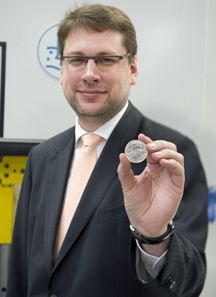 Eduard Stiprais, Ambassador of Latvia to the United Kingdom holds one of the new re-dated 5 Lats coins on 28 May 2012.