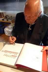 Peter Götz Güttler beim Signieren des Buchs.