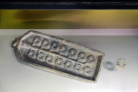 Positivmodell für die Herstellung von Gussformen für Münzen, 221-207 v. Chr., Bronze, L. 29,9, B. 10,9, H. 2 cm. Fundort: Lintong, Xi'an, ausgegraben 1983. Dieses Positivmodell diente dazu, Gussformen für die runden Münzen des Qin-Reiches im Wert einer halben Unze (banliang) herzustellen. © Bernisches Historisches Museum, Bern.