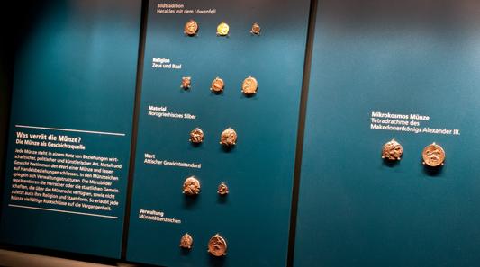Teilansicht der Vitrine über die Aussagemöglichkeiten von Münzen, veranschaulicht am Beispiel der Tetradrachme Alexanders des Großen.