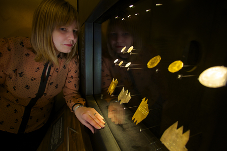 Dr Megan Gooch looks at a case of rare coins at the launch of the new exhibition. © Historic Royal Palaces.