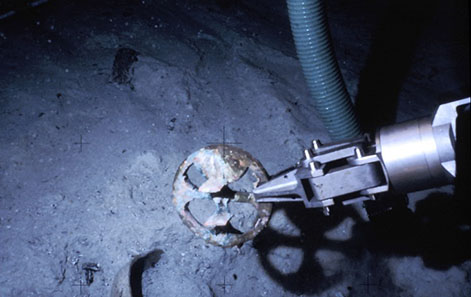 The ROV's manipulator arm retrieves a rare bronze mariner's astrolabe, one of three recovered from the 1622 Tortugas shipwreck site. Photo: Odyssey Marine Exploration, Inc., www.shipwreck.net.